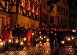 Silvesterumzug: Menschen laufen mit Laternen abends durch Schiltach