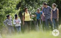 Monika Wurft mit einer Familie bei einer Kräuterwanderung