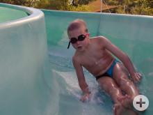 Ein Junge mit Schwimmbrille auf der Freibad-Rutsche
